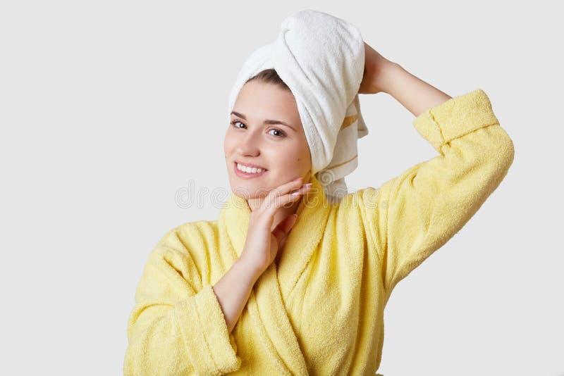 Abrandamento e harmonia após termas A mulher europeia bonita nova tem a toalha na cabeça, veste o roupão, tem o sorriso encantado fotografia de stock