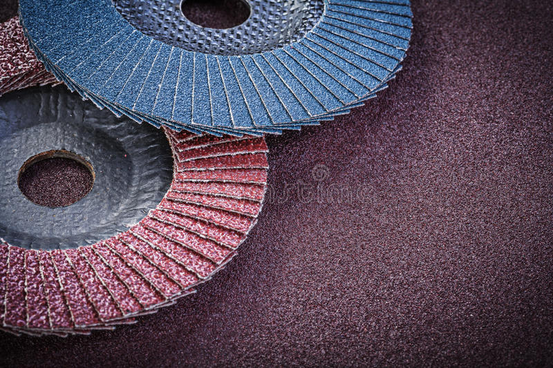 Abrasive flap wheels on sandpaper sheet top view.  royalty free stock photos