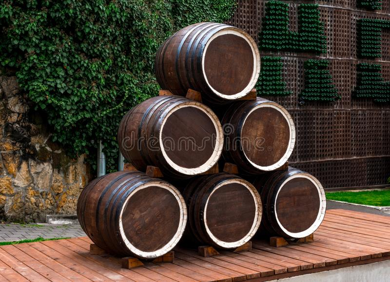 Abrau-Durso, wooden wine barrels made up of a pyramid on a platform of boards, in the background a stone wall overgrown with vines stock photos