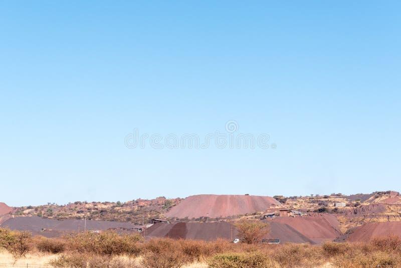 Abraumhalden und Berge des Eisenerzes an einem Bergwerk stockbild