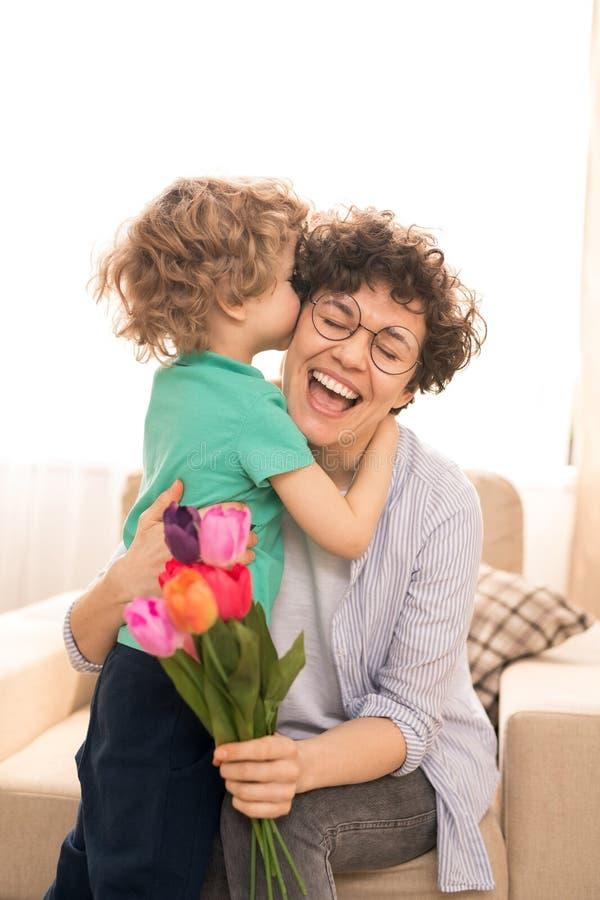 Abrazando y besando a la mamá fotografía de archivo