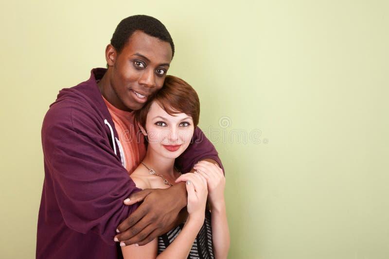 Abrazo adolescente de los pares de la raza mezclada fotografía de archivo libre de regalías