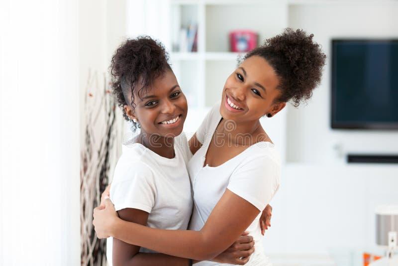 Abrazo afroamericano del retrato de los mejores amigos del teeange - p negro imagenes de archivo