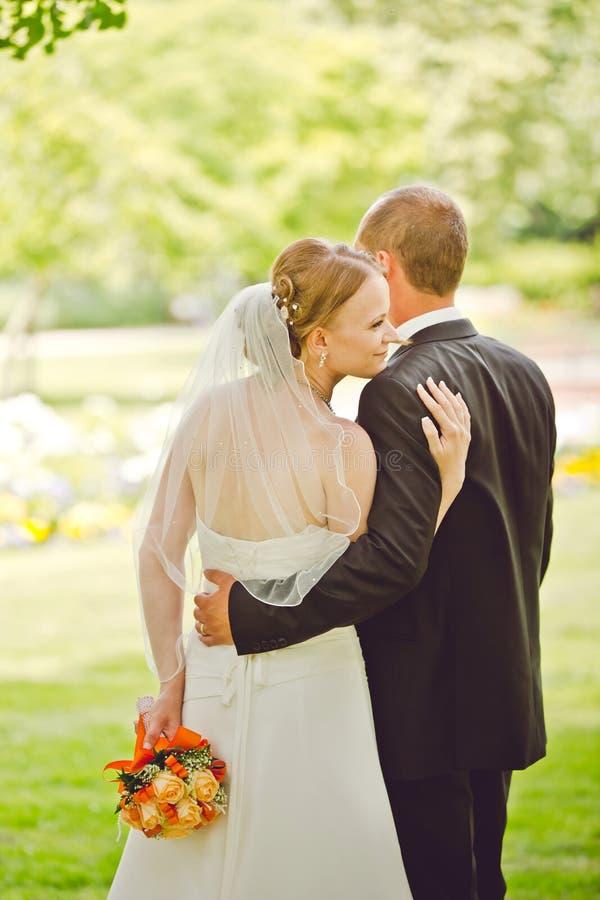Abrazo atractivo del novio y de la novia fotografía de archivo libre de regalías