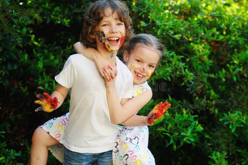 Abrazo de los niños, sus caras y manos en pintura fotos de archivo