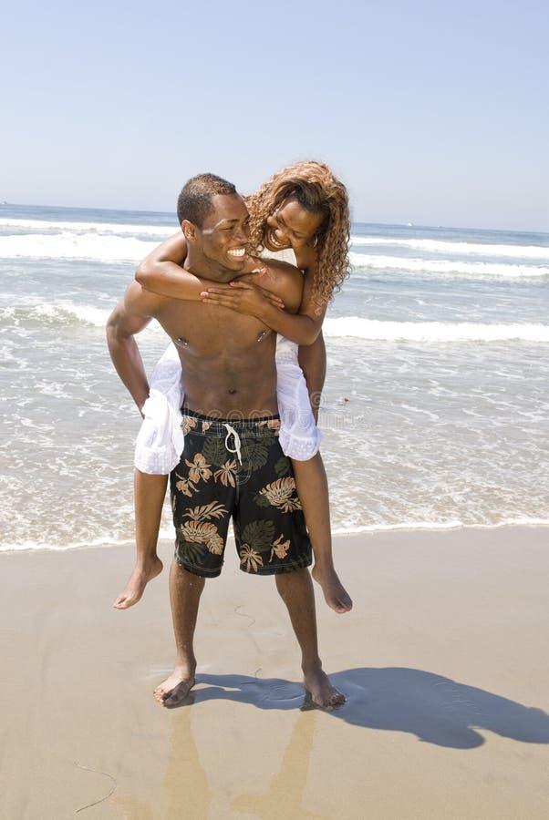 Abrazo de los pares del afroamericano en la playa fotografía de archivo