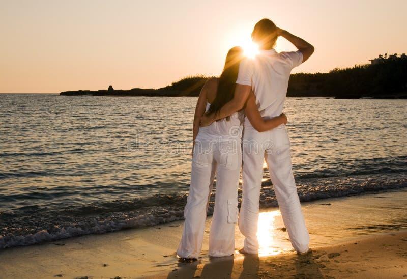 Abrazo de los pares, disfrutando de puesta del sol del verano. fotografía de archivo libre de regalías