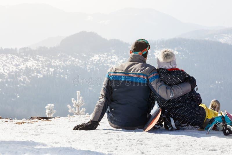 Abrazo de los pares que se sientan en nieve y que gozan en paisaje imagen de archivo