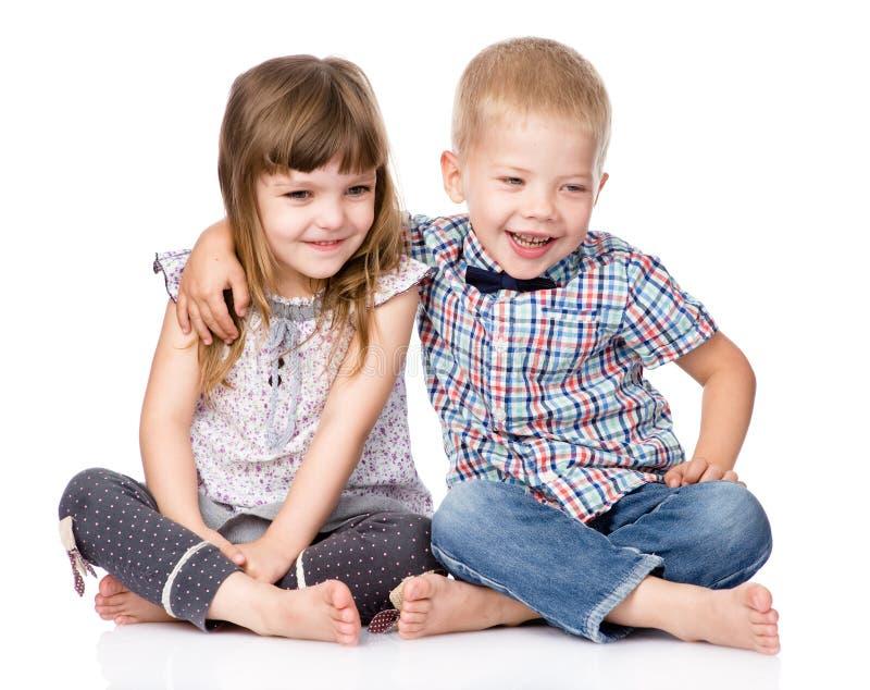 Abrazo del hermano sonriente y de la pequeña hermana Aislado fotos de archivo libres de regalías