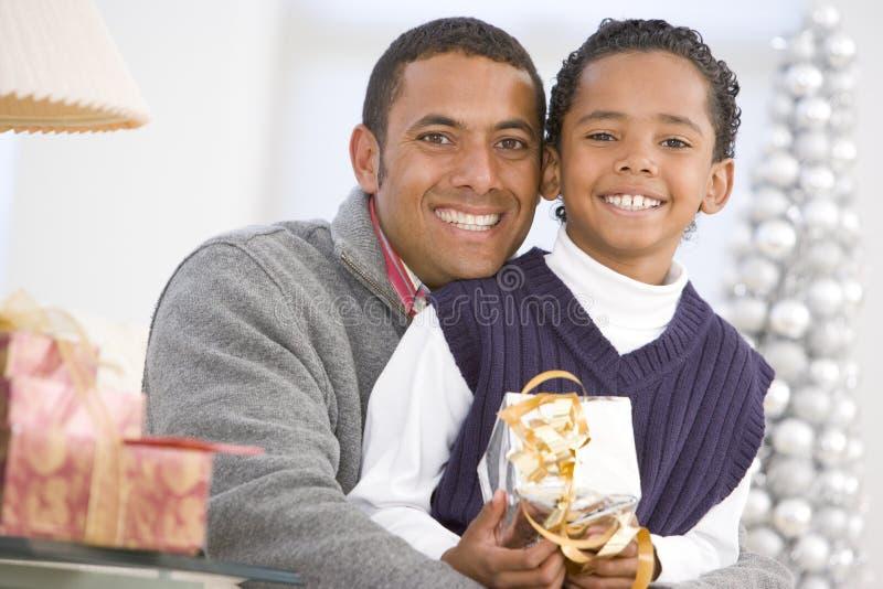 Abrazo del padre y del hijo, celebrando el regalo de la Navidad imagen de archivo