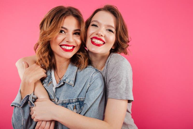 Abrazo feliz de dos amigos de las mujeres foto de archivo