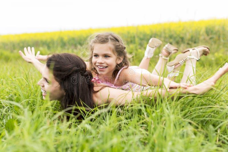 Abrazo feliz de la hija de la madre y del niño de la familia en las flores amarillas en la naturaleza en verano imágenes de archivo libres de regalías