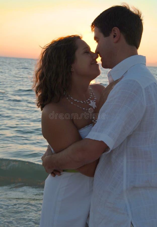 Abrazo feliz de los pares en la playa fotografía de archivo libre de regalías