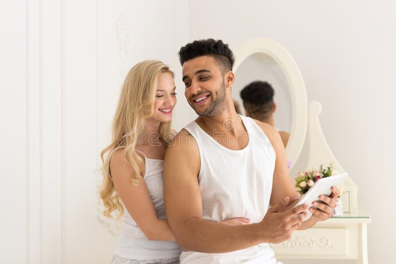 Abrazo hermoso de los pares usando hombre hispánico joven y mujer de la sonrisa feliz de la tableta en amor fotos de archivo libres de regalías