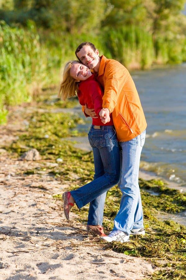 Abrazo joven de los pares del amor en la costa del río imagen de archivo