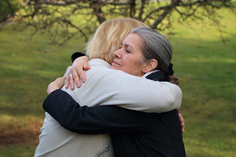 Abrazo maduro de dos amigos fotos de archivo