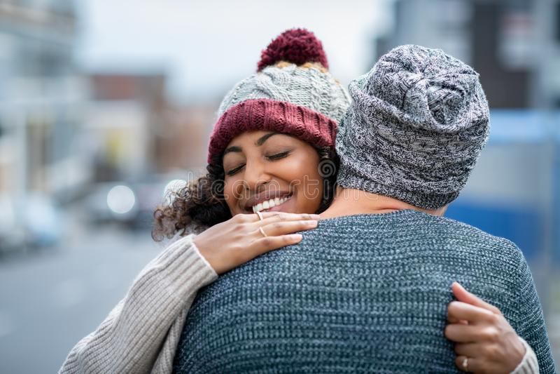 Abrazo multiétnico de los pares al aire libre en invierno fotografía de archivo
