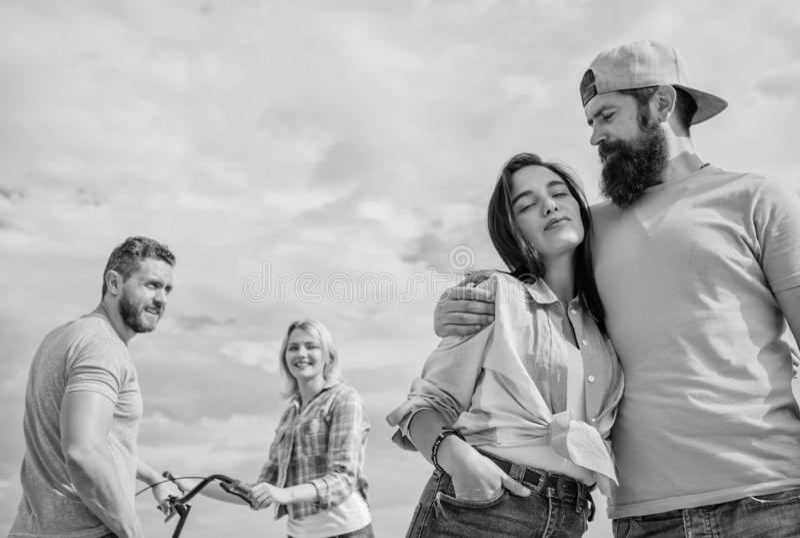 Abrazo relajado del hombre y de la mujer feliz junto mientras que el hombre en fondo intenta coger a la nueva novia Relaciones a  imagen de archivo