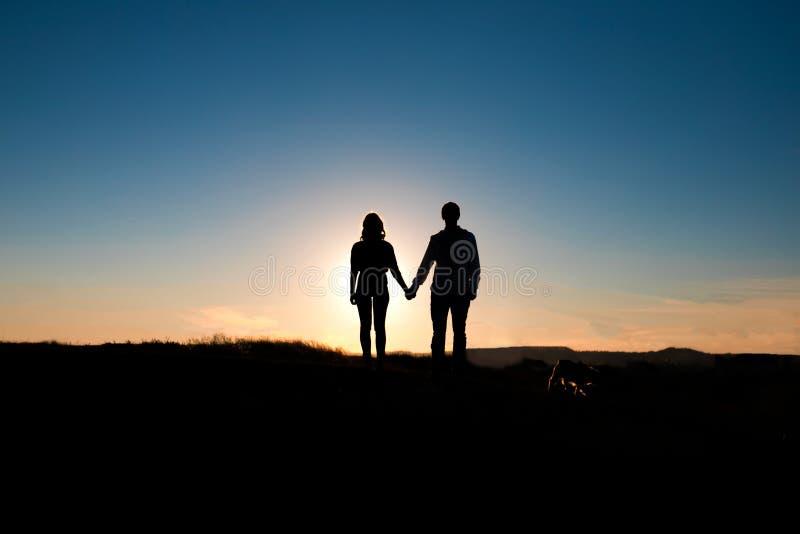 Abrazo romántico de los pares en la puesta del sol en fondo fotos de archivo libres de regalías