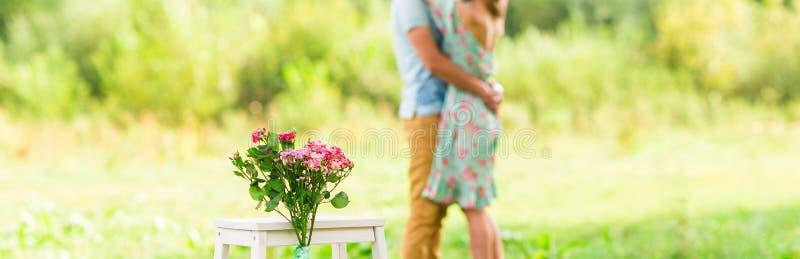 Abrazo romántico feliz de los pares Foco en las flores Focuse selectivo fotos de archivo