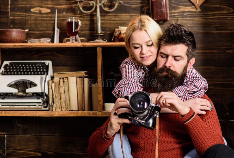 Abrazos de los pares en interior de madera del vintage El hombre con la barba, fotógrafo en cara ocupada sostiene la cámara pasad imagen de archivo