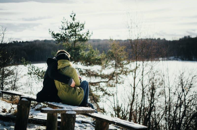Abrazos de los pares de la felicidad El hombre joven abraza a la muchacha en invierno fotos de archivo libres de regalías