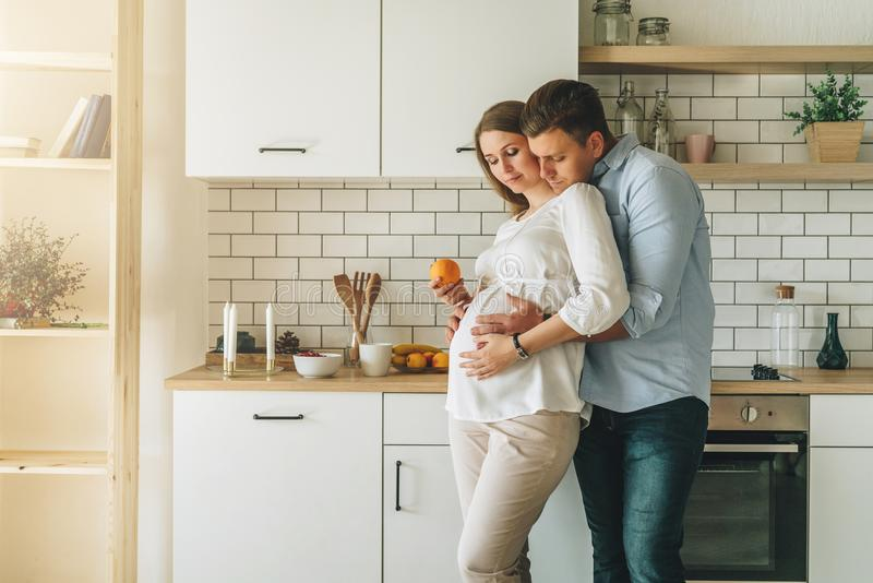 Abrazos de los pares que colocan la tabla cercana en cocina El marido abraza a su esposa embarazada, poniendo sus manos en su vie fotografía de archivo libre de regalías