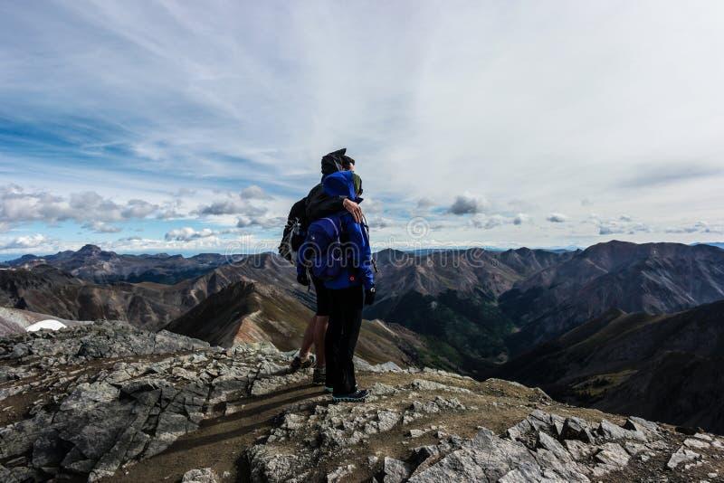 Abrazos de un par encima de una montaña en los Colorado Rockies imágenes de archivo libres de regalías