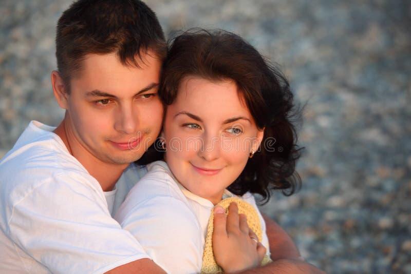 Abrazos jovenes de los pares en la playa fotografía de archivo