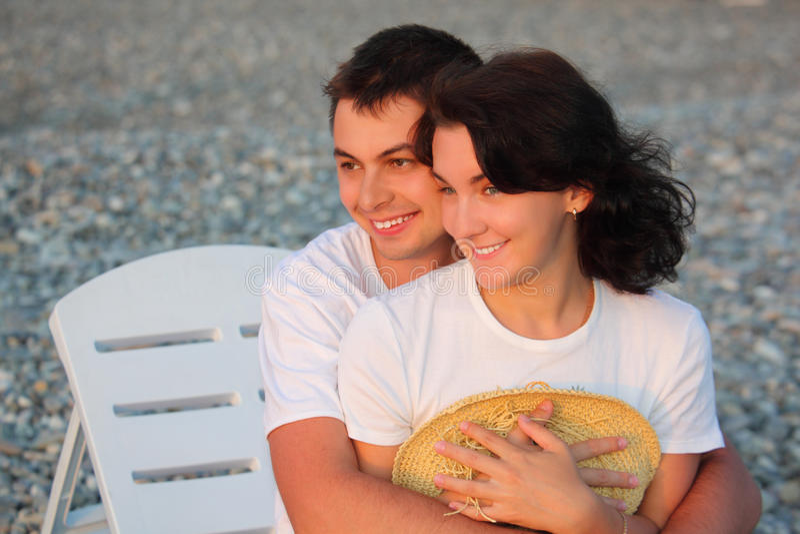 Abrazos jovenes de los pares en la playa imagen de archivo libre de regalías