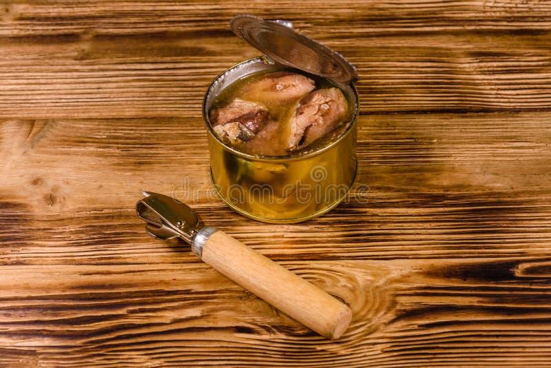 Abrelatas y lata con la sardina en la tabla de madera imagenes de archivo