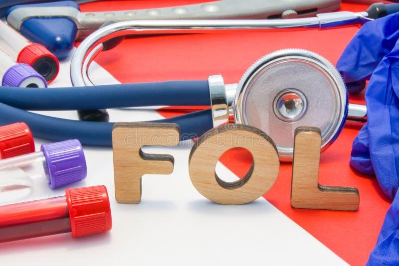 Abreviatura médica de FOL que significa el folato total o el ácido fólico en diagnósticos del laboratorio en fondo rojo El nombre imagen de archivo