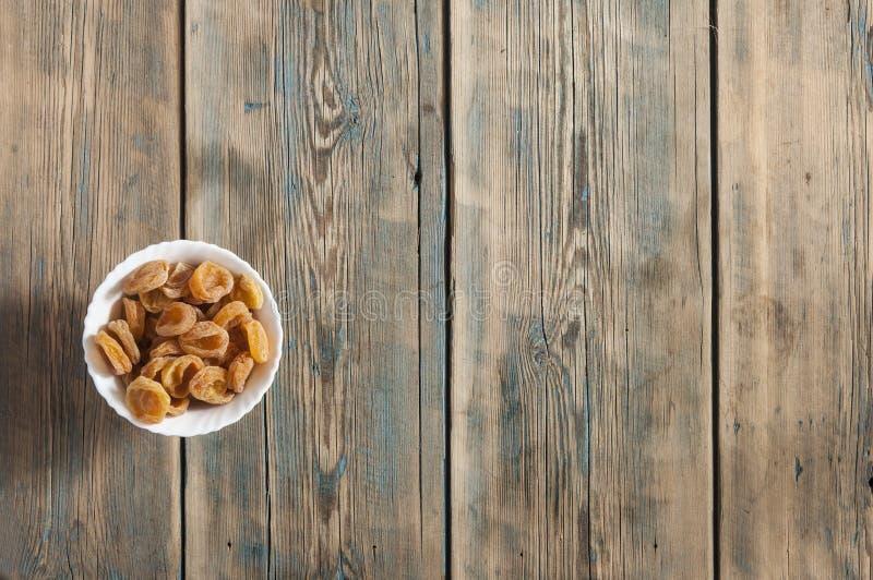Abricós secados na bacia no fundo de madeira, vista superior fotografia de stock royalty free