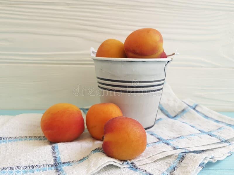 Abricot frais sur un seau en bois bleu de fond photo stock