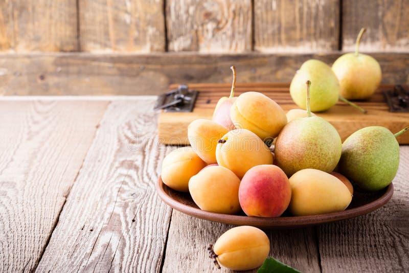 Abricots et poires organiques mûrs sur la table en bois rustique photos stock