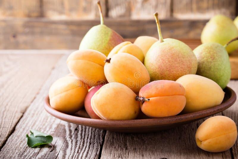 Abricots et poires organiques mûrs sur la table en bois rustique image stock