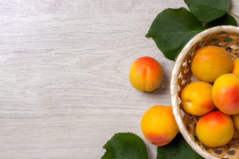 Abricots frais dans le panier sur une table en bois photos libres de droits