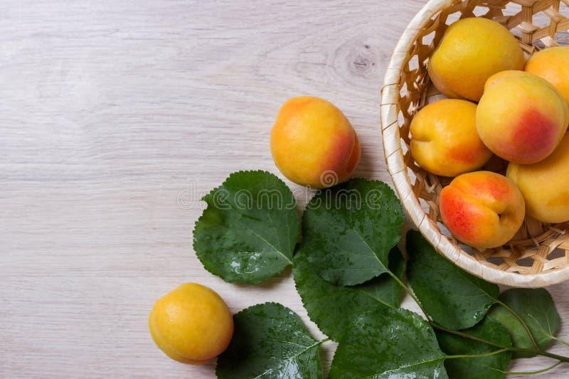 Abricots frais dans le panier sur une table en bois photo stock