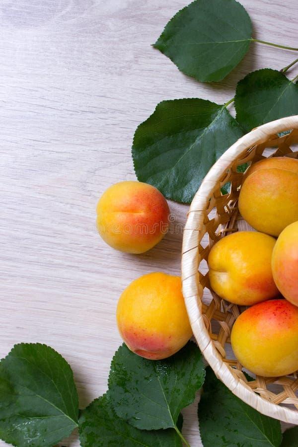Abricots frais dans le panier sur une table en bois image libre de droits