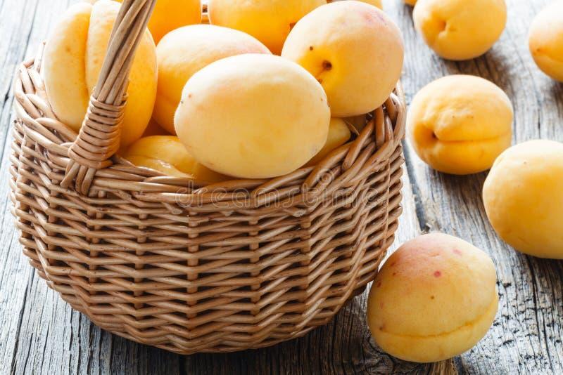 Abricots frais dans le panier sur une table en bois photos stock