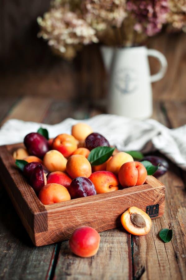 Abricots frais dans une boîte en bois sur le fond de vintage photographie stock