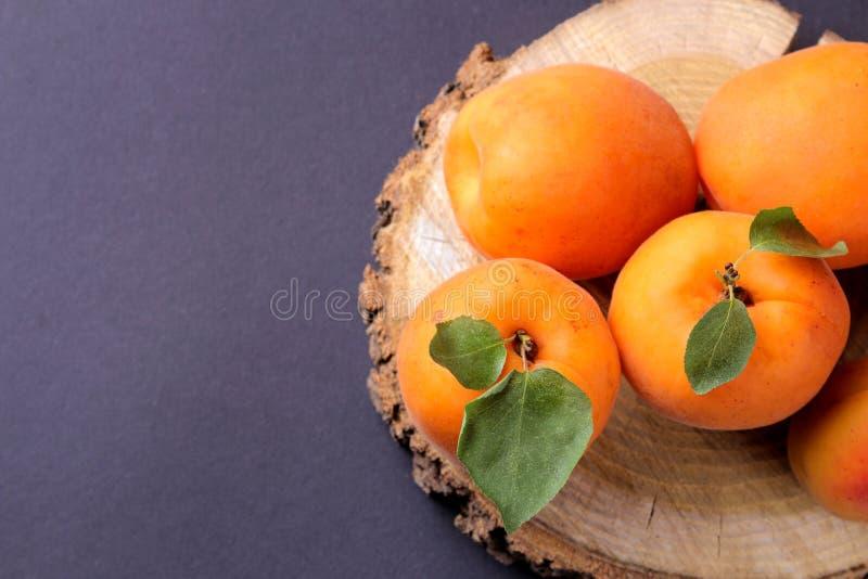 Abricots frais et m?rs sur un support en bois sur un fond noir photographie stock libre de droits