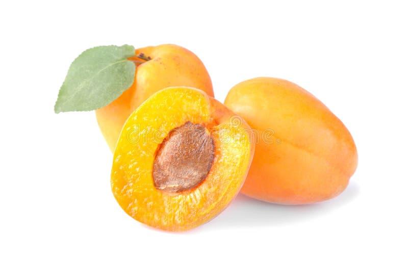 abricots frais et une moitié d'abricot avec une feuille sur un fond blanc d'isolement photos stock