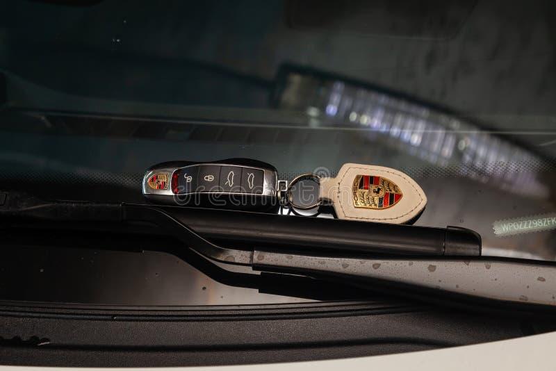 Abridor remoto da porta da chave do carro com um keychain de couro de Porsche Cayman que encontra-se no para-brisa nos limpadores foto de stock