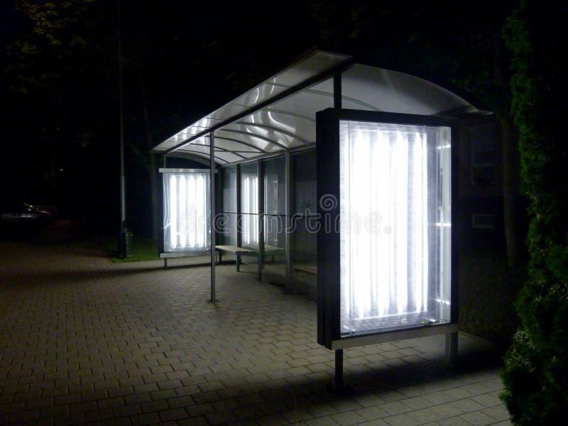 Abrigo de ônibus iluminado na noite na vizinhança residencial foto de stock royalty free