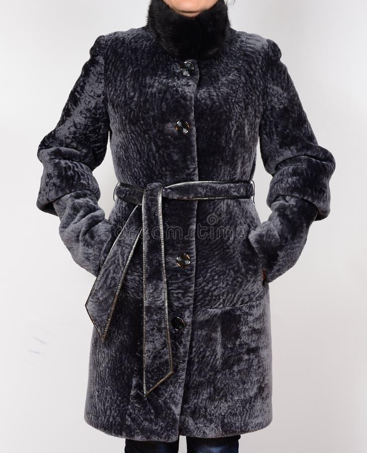 Abrigo de pieles de la zalea aislado en fondo gris Abrigo de pieles en modelo sin la cara imagenes de archivo