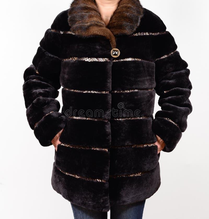 Abrigo de pieles de la zalea aislado en fondo gris Abrigo de pieles en modelo sin la cara outerwear Abrigo de pieles imagen de archivo