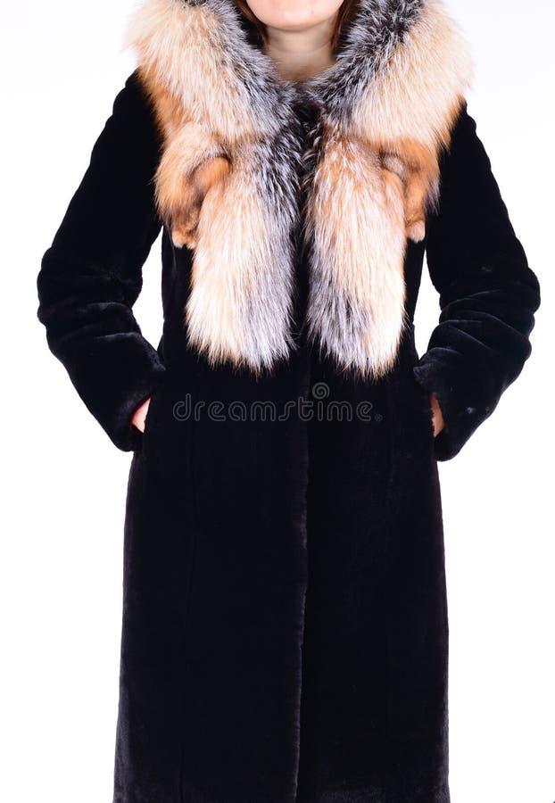Abrigo de pieles negro de la zalea con el cuello del zorro aislado en fondo gris Abrigo de pieles en modelo sin la cara outerwear imágenes de archivo libres de regalías