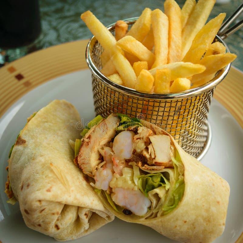 Abrigo vegetal del camarón y del pollo cortado por la mitad con las patatas fritas imagen de archivo
