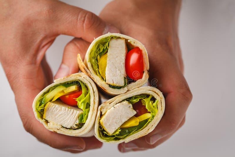 Abrigos asados a la parrilla del burrito con el pollo y las verduras en las manos, top imagenes de archivo